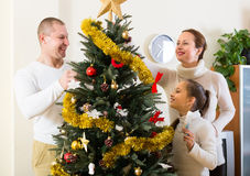 Family decorating Christmas tree. Smiling parents and child decorating Christmas tree at living room. Focus on girl Stock Photography