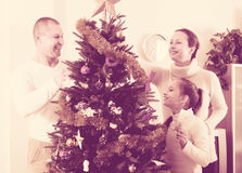 Family decorating Christmas tree. Smiling parents and child decorating Christmas tree at living room. Focus on girl Royalty Free Stock Photography