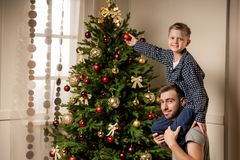 Family decorating christmas tree together. Young father and little son in pajamas decorating christmas tree together at home Royalty Free Stock Image