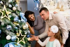 Family decorating a Christmas tree. Young man with his daughter helping her decorate the Christmas tree. stock photography
