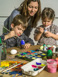 Family decorating Easter eggs. Photo of a mother and her children painting and decorating hard-boiled eggs for easter Stock Photos