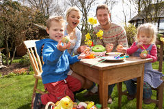 Family Decorating Easter Eggs On Table Outdoors. In the sun Stock Images