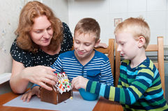 Family decorating gingerbread house Stock Photography
