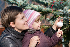 Family decorating New Year tree with toy ball Stock Photo