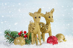 The family of deer with branch fir and holly leaves in the snow. Royalty Free Stock Photo