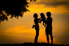 Family. This is the definition of a happy family. Mother, father and their child watching a beautiful sunset Stock Image