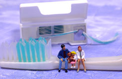 Family Dental. Miniature People Sitting on a Toothbrush.  Family or Pediatric Dental Concept Royalty Free Stock Photos