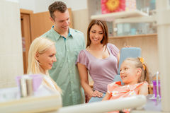 Family At The Dentist. Happy family at visit in the dentist office. Female dentist talking with little girl, her parents standing next to her Stock Image