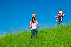 Family Desceding A Hill. A family with 2 daughters is coming down a hill with tall grass Stock Photos