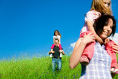Family Desceding A Hill. A family with 2 daughters is coming down a hill with tall grass Stock Images