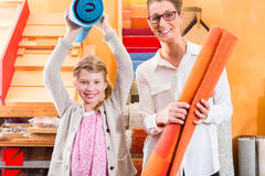 Family Designer buying rug or carpeting. In home improvement store Stock Photo