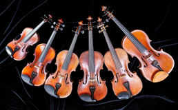 Family of different sized violins on black Royalty Free Stock Images