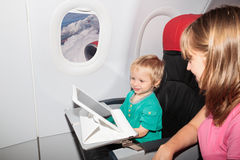 Family with digital tablet in plane. Family with touch pad on plane in flight Royalty Free Stock Photo