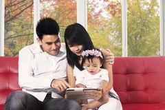 Family with digital tablet sitting on coach Stock Image