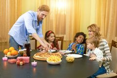 Family at the dining table. Kids and parents, pizza Royalty Free Stock Photos