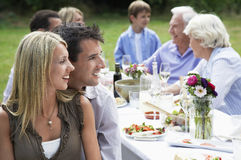 Family Dining At Table In Garden Stock Photo