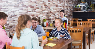 Family dining and talking. Glad parents with children having conversation at dining table in cafe Royalty Free Stock Photo