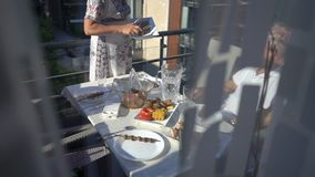 Family dinner on the balcony of the apartment. In summer stock video footage