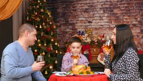 Family dinner at the Christmas tree. The whole family raises wine glasses and drinks from them stock video