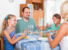 Family dinner. Friendly mother, father and kids sitting at the table at a home and eating Royalty Free Stock Photo