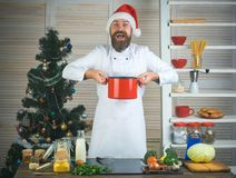 Family dinner and new year recipe. Christmas cookies at man cook in kitchen. Chef man in santa claus hat cooking. Thanksgiving day and Christmas. New year royalty free stock photos