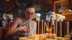 Family dinner at pan-Asian restaurant. Girl eating rolls with chopsticks. Close-Up Young Girl Eating Sushi with Chopsticks in a Japanese Restaurant stock footage