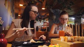 Family dinner at pan-Asian restaurant. Mother and daughter eating with wooden chopsticks rolls. Big set on sushi and. Mother and daughter eating with wooden stock video