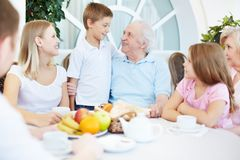 Family dinner. Portrait of senior and young couples with their children having dinner at home Stock Image