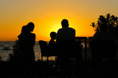 Family Dinner in the Setting Tropical Sun. Panglao, Bohol - Philippines - January 21, 2016: A tourist family with nanny enjoys a sunset dinner during their Stock Photography