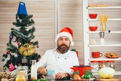 Family dinner at Thanksgiving day, Christmas or New year. With holiday food. Christmas cookies at man cook in kitchen in chef uniform and santa claus hat stock photo