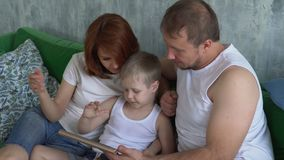 The family discusses information on the tablet. The son shows to the parents something on the tablet.. stock video