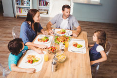 Family discussing with food on dining table Stock Image