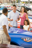 Family discussing new car with salesman. On lot stock images