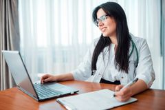 Family doctor concept, specialist sits at laptop. Professional health care Stock Photography