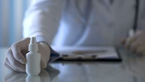 Family doctor giving nasal spray to patient, cold treatment, medicine, close up stock photo