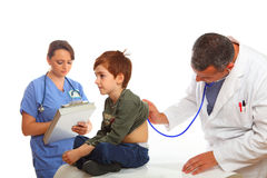 Family Doctor with Nurse examining a boy Stock Photo