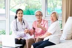 Family doctor or nurse wearing white coat and stethoscope with smiling senior patient during home visit,young female home caregive. R,health visitor holding stock photos