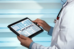 Family doctor reading Smoking diagnosis in digital medical repor Royalty Free Stock Images