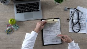 Family doctor signing prescription and health insurance form, health care reform stock images