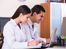 Family doctors with stethoscope working in office together Stock Photos