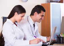Family doctors with stethoscope working in office together Royalty Free Stock Photography