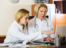 Family doctors therapeutists discussing difficult case in office Stock Image