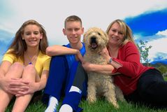 Family with dog. Mather children and their dog on grass area Stock Photo
