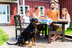 Family with dog eating in garden front of house Stock Photos