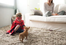 Family with dog at home. Cute superhero child and mother spending time together in the living room playing with dog Stock Photography