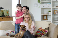 Family with dog at home. Female couple with son and pet dog posing for the camera in their home Stock Photos