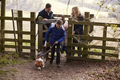 Family with a dog passing through a gate in the countryside Royalty Free Stock Images