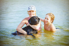 Family with dog playing in water Stock Photos