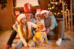 Family and dog sitting by Christmas tree Royalty Free Stock Images