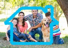 Family with dog sitting in the park with home outline Stock Photography